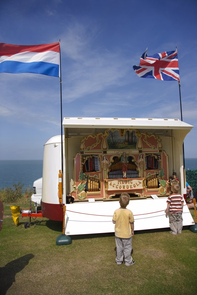 England, Kent, Whitstable. Two young boys looking at a 41-key Heesbeen 'Magic Accordeola' fair organ by the seafront at a fair in Whitstable. : Stock Photo