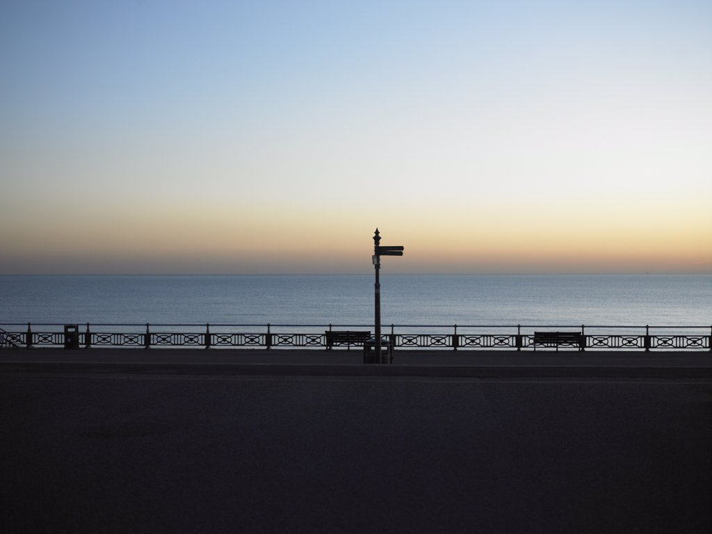 England, East Sussex, Hove. A view out to a calm sea at dusk from the promenade in Hove. : Stock Photo