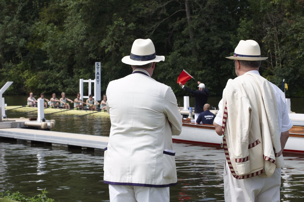 England, Oxfordshire, Henley-on-Thames. Senior rowing club members standing on the riverside watching the start of a race at the annual Henley Royal Regatta. : Stock Photo