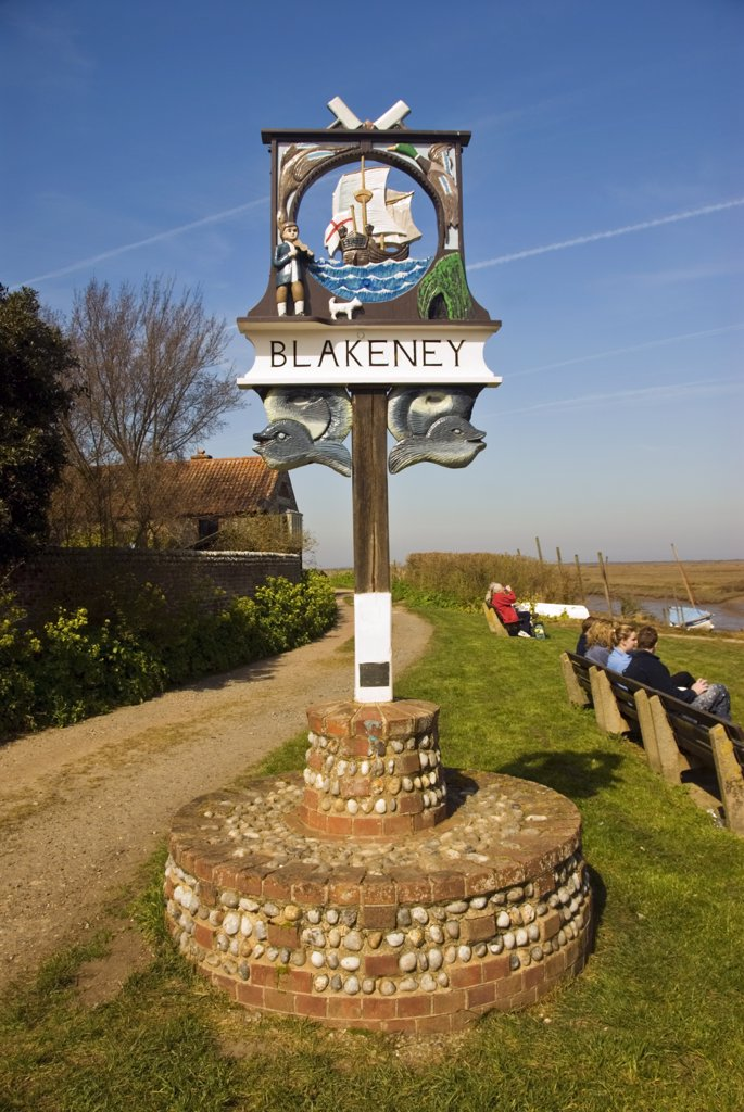 England, Norfolk, Blakeney. Old village sign in Blakeney. The sign shows a fiddler and his dog and the story goes that this fiddler went to explore a tunnel with his dog and both were never seen again. : Stock Photo