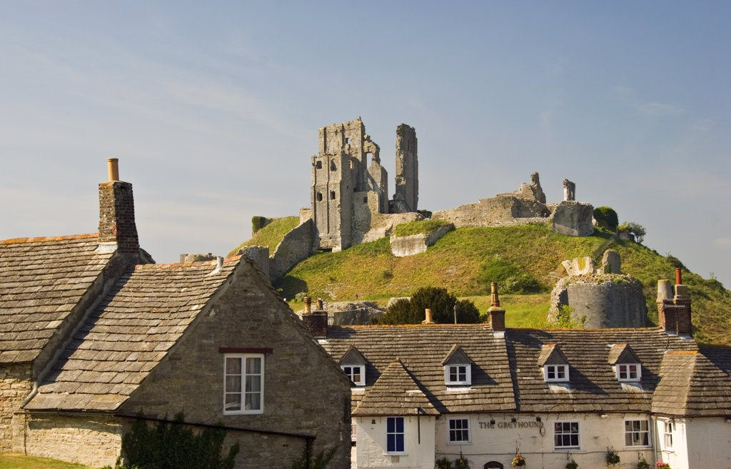 England, Dorset, Corfe. A view over the rooftops of Corfe village towards Corfe Castle. : Stock Photo