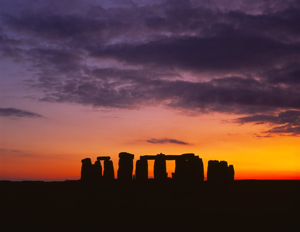 England, Wiltshire, Stonehenge. The Stonehenge trilithons silhouetted after sunset. : Stock Photo