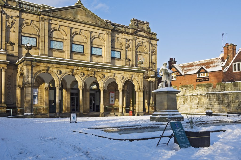 Stock Photo: 4282-14728 England, North Yorkshire, York. The statue of York artist William Etty, erected in 1911, in the snow covered Exhibition Square outside York Art Gallery (City Art Gallery) in winter.