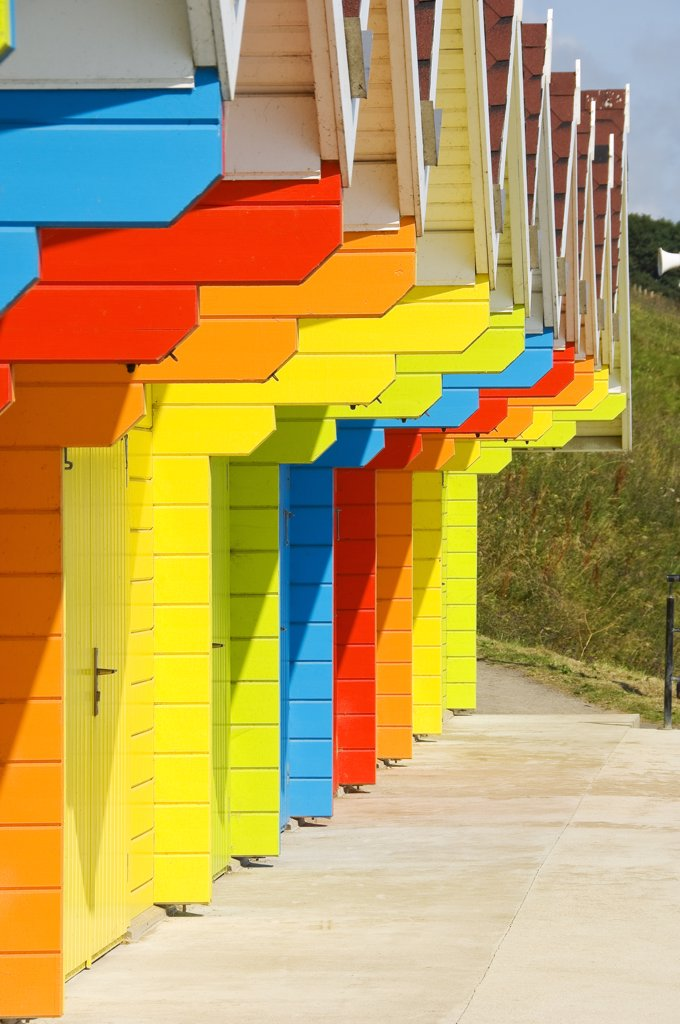 England, North Yorkshire, Scarborough. A row of colourful beach huts at North Bay. : Stock Photo