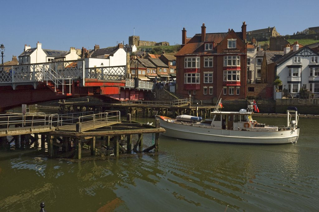 Stock Photo: 4282-15314 England, North Yorkshire, Whitby. A boat passing through the swing bridge in Whitby.