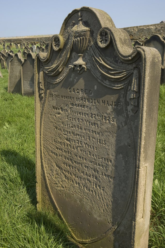 Stock Photo: 4282-15333 England, North Yorkshire, Whitby. A weathered headstone in St Mary's churchyard.