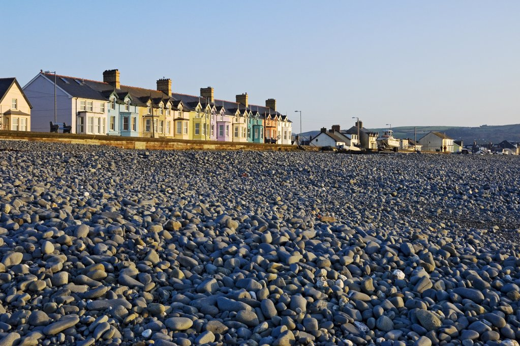 Wales, Ceredigion, Borth. View over a pebble beach towards colourful houses along the seafront at Borth. : Stock Photo