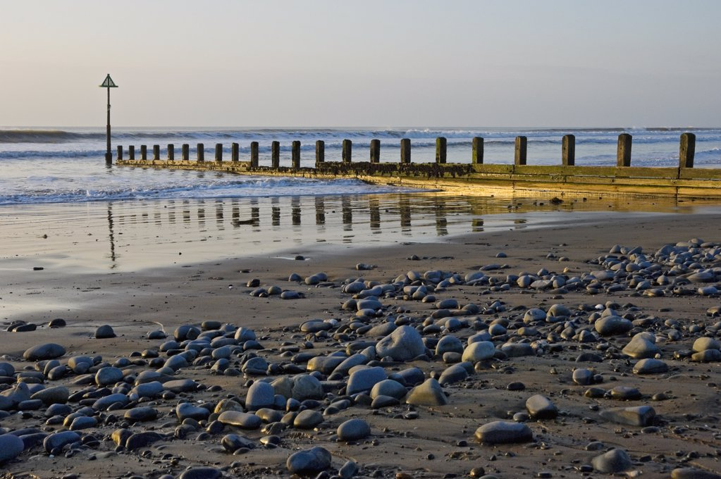 Stock Photo: 4282-15502 Wales, Ceredigion, Borth. Waves rolling onto the beach past a breakwater.