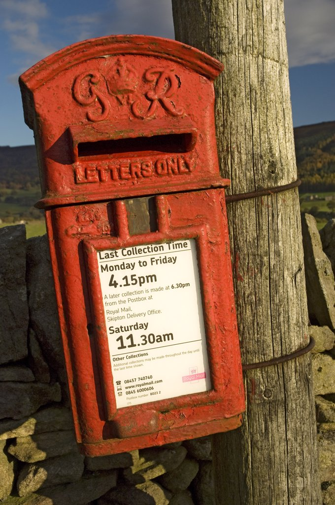 England, North Yorkshire, Upper Wharfedale . Old letterbox on a wooden post. : Stock Photo