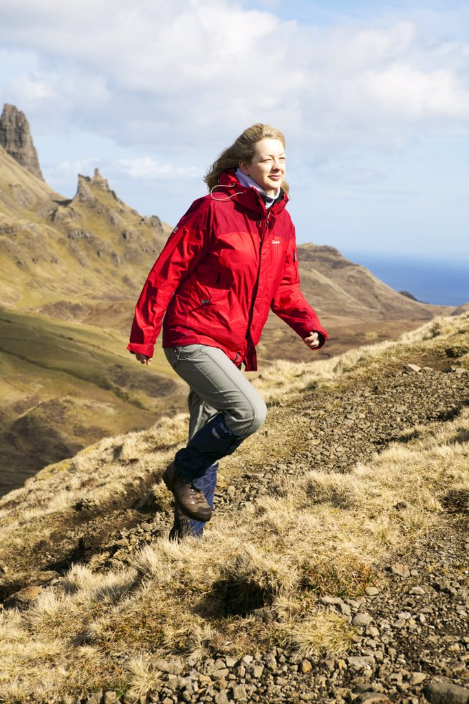 Scotland, Isle of Skye, Trotternish. A female walker wearing a red waterproof climbing up a path over the Quiraing. : Stock Photo