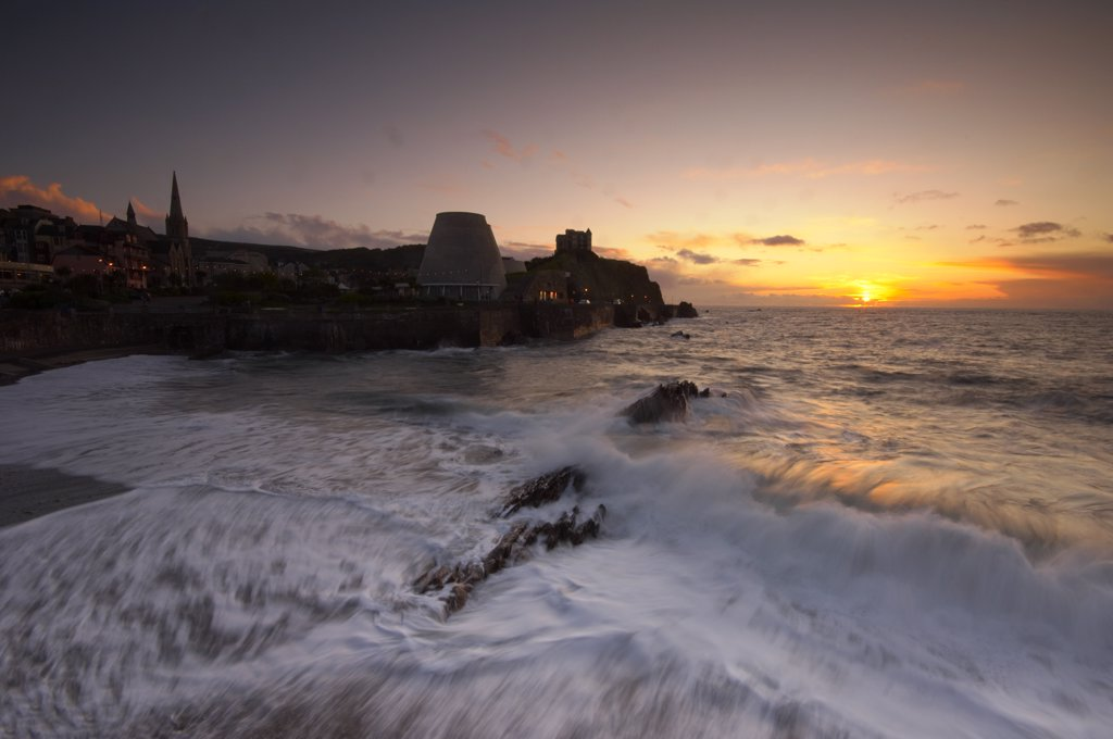 England, Devon, Ilfracombe. Rough seas rushing onto the town beach at sunset at Ilfracombe in North Devon. : Stock Photo