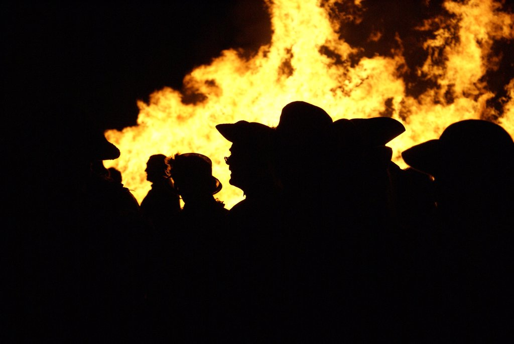 England, East Sussex, Hastings. People in Traditional costume silhouetted against bonfire flames. : Stock Photo