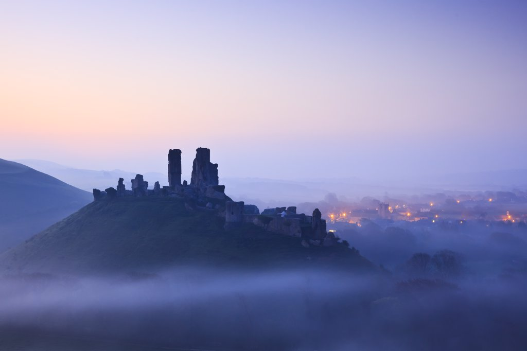 England, Dorset, Corfe Castle. Corfe Castle, dating back to the 11th century, rising above pre-dawn mist. : Stock Photo