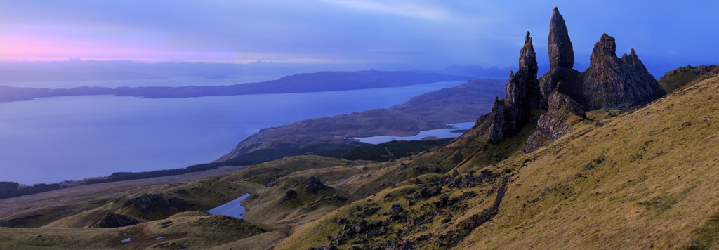 Stock Photo: 4282-1675 Scotland, Isle of Skye, Trotternish. Panoramic view of the Old Man of Storr, dramatic pinnacles of rock remaining from ancient landslips on the Trotternish peninsula with the Cuillin ridge in the background.