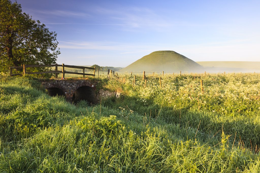 England, Wiltshire, Silbury Hill. Silbury Hill, an artificial chalk mound, the tallest prehistoric human-made mound in Europe, on a misty summer morning. : Stock Photo