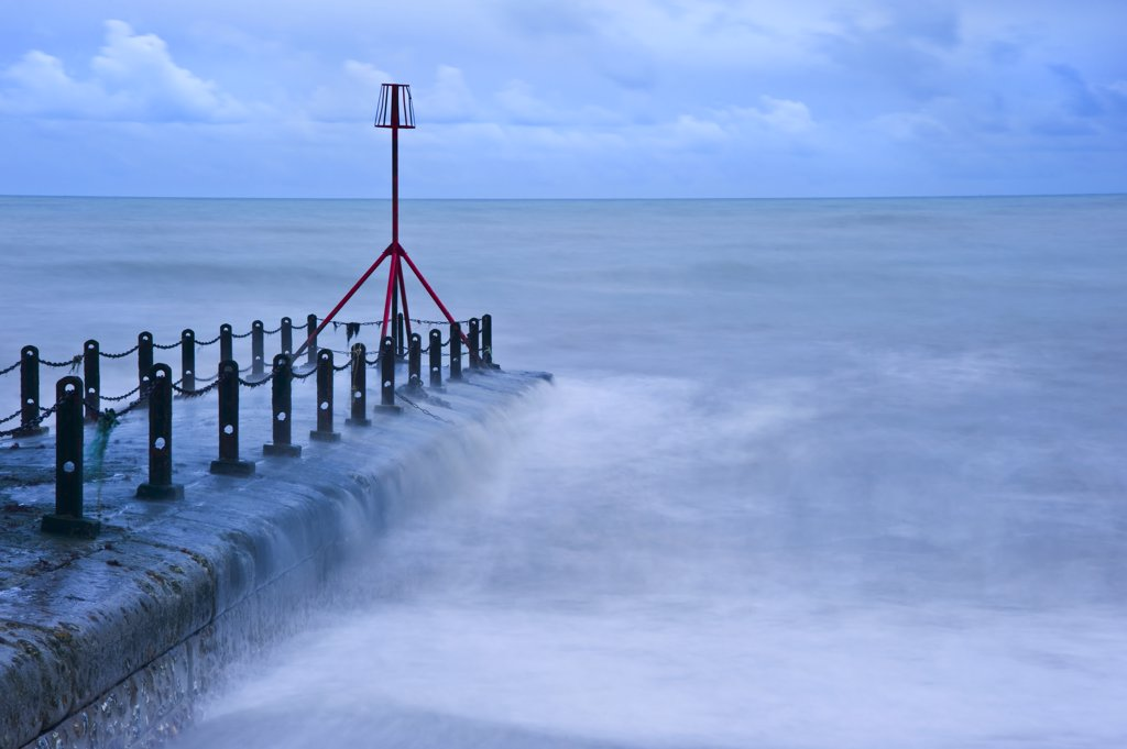 Stock Photo: 4282-16837 England, City of Brighton and Hove, Hove. Waves breaking around a red beacon at the end of a breakwater.