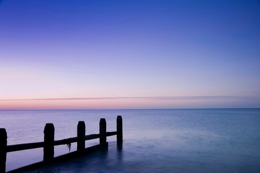 Stock Photo: 4282-16850 England, West Sussex, Worthing. A groyne leading out from the beach at Worthing into a calm sea at sunrise.