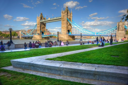 England, London, South Bank. People walking along the south bank of the River Thames with Tower Bridge, one of London's most iconic landmarks in the background. : Stock Photo