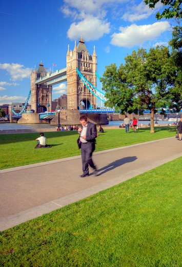 Stock Photo: 4282-17073 England, London, South Bank. People walking along the south bank of the River Thames with Tower Bridge, one of London's most iconic landmarks in the background.