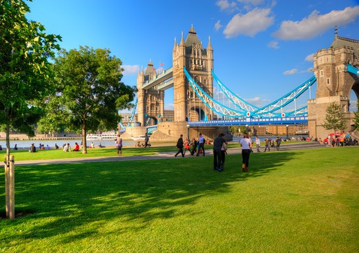 Stock Photo: 4282-17074 England, London, South Bank. People walking along the south bank of the River Thames with Tower Bridge, one of London's most iconic landmarks in the background.
