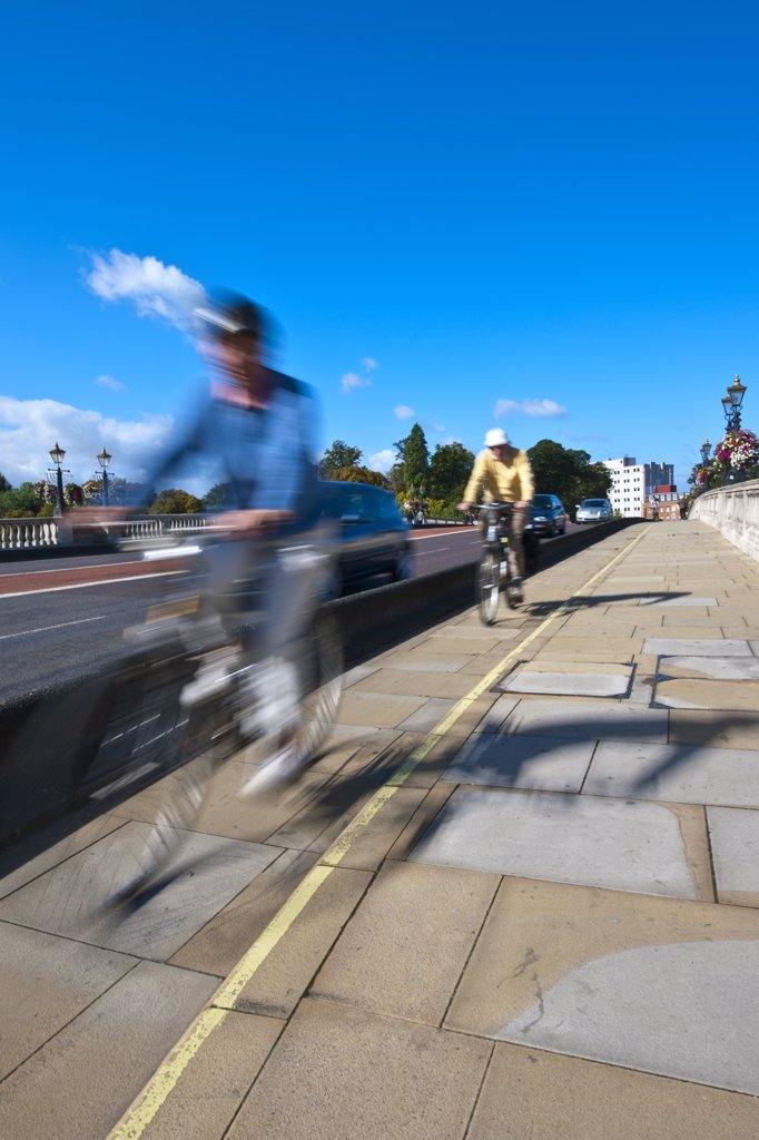 England, Surrey, KIngston upon Thames. Cyclists riding in a cycle lane over Kingston Bridge. : Stock Photo