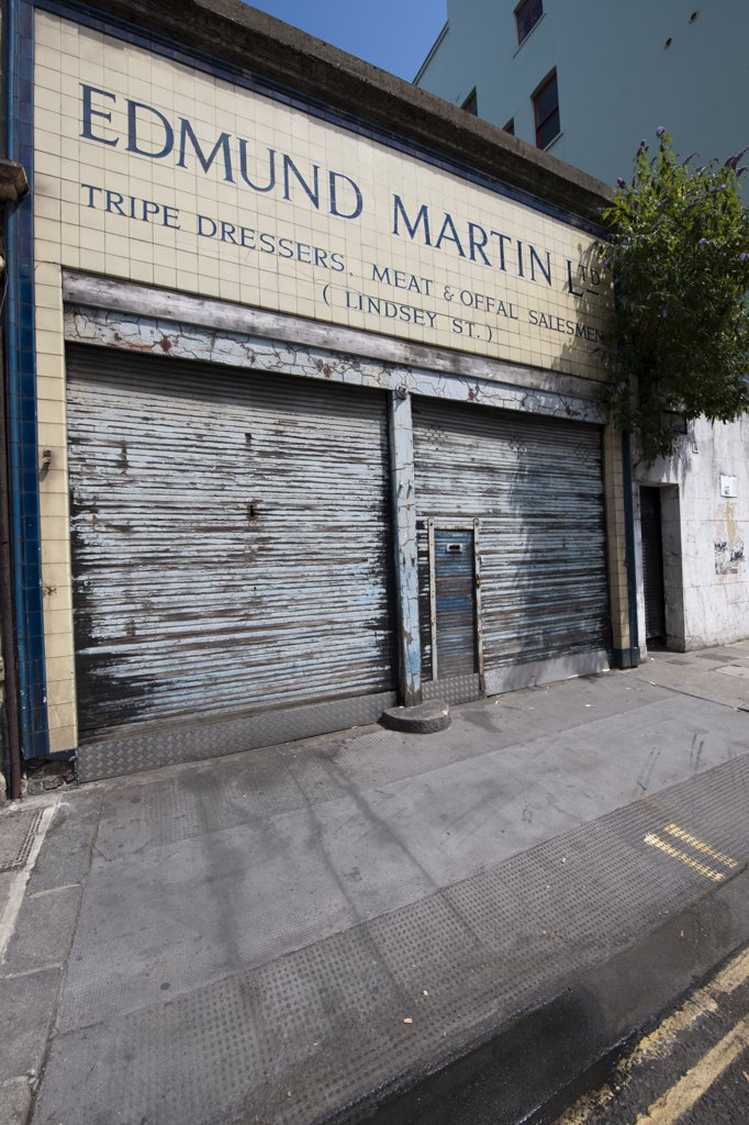 England, London, City of London. Peeling shutters on a vacant shop in Lindsey Street, Smithfield, with a tree growing out of wall. : Stock Photo