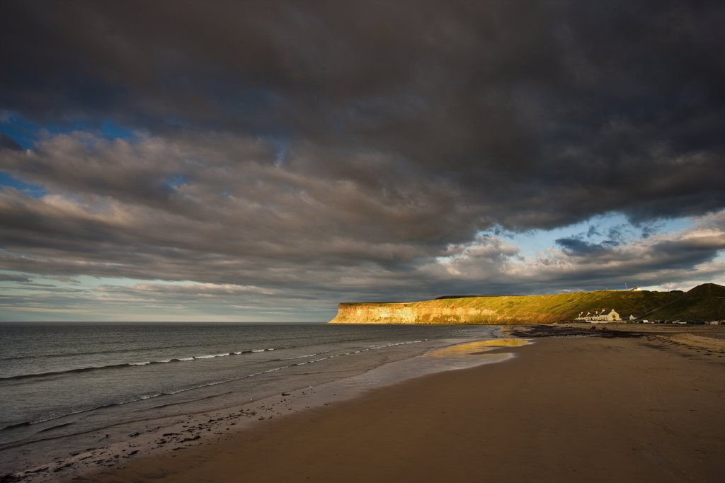 England, Redcar & Cleveland, Saltburn-By-The-Sea. Shaft of Sunlight on Huntcliff, a large vertical cliff a mile east of Saltburn. : Stock Photo