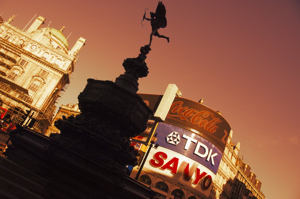 England, London, Piccadilly Circus. The statue of Eros on the Shaftesbury memorial fountain at Piccadilly Circus in London's West End silhouetted against advertising displays in the background. : Stock Photo