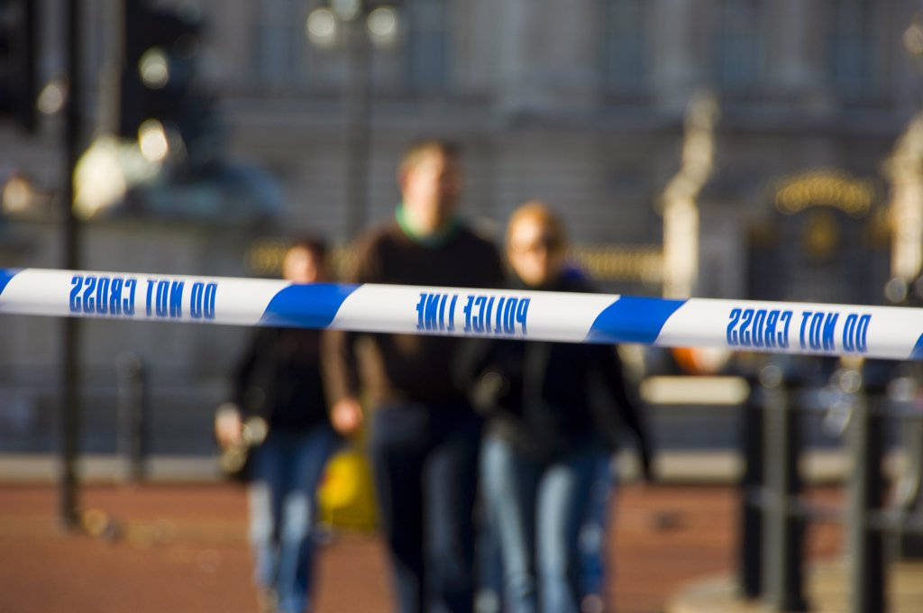 Stock Photo: 4282-17684 England, London, Westminster. Do Not Cross, Police Line tape stretched across a road in central London with pedestrians in the background.