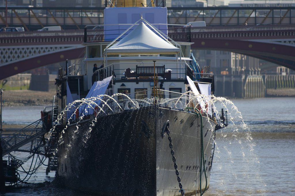 Stock Photo: 4282-17724 England, London, Victoria Embankment. Water being pumped from HMS President, an events venue permanently moored on Victoria Embankment in central London with Blackfriars Bridge in the background.