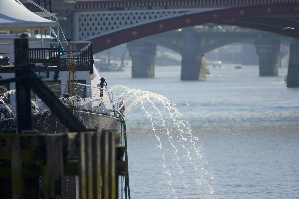 England, London, Victoria Embankment. Water being pumped from HMS President, an events venue permanently moored on Victoria Embankment in central London with Blackfriars Bridge in the background. : Stock Photo