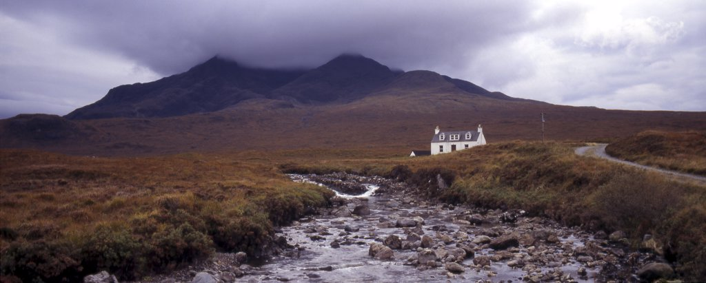 Scotland, Isle of Skye, Glen Sligachan. Panoramic view of cottage with river in foreground and cloud covered mountains in the background. : Stock Photo