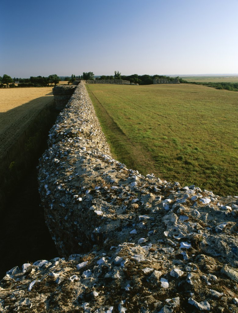 Stock Photo: 4282-17986 England, Norfolk, Burgh Castle. Looking from the NE corner tower along the southern wall and projecting bastions of Burgh Castle Roman Fort, a rectangular fort built by the Romans in the 3rd century AD against Saxon raiders.