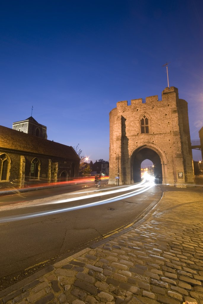 Stock Photo: 4282-1805 England, Kent, Canterbury. The Westgate Tower in Canterbury lit up at night with trials of light from passing traffic.