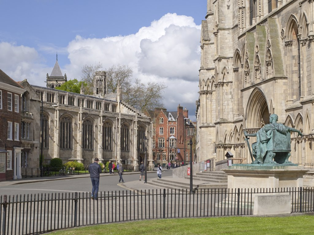 Stock Photo: 4282-18464 England, North Yorkshire, York. St. Michael Le Belfrey church where Guy Fawkes was christened in 1570 opposite a bronze statue of Constantine I outside York Minster.