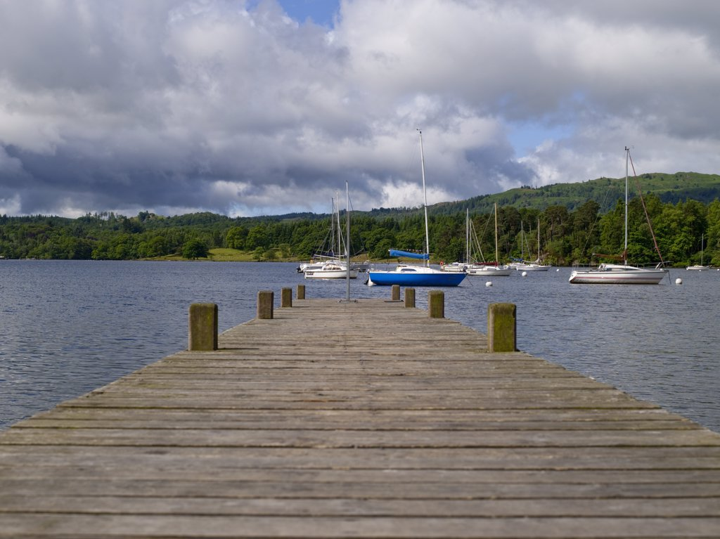 England, Cumbria, Ambleside. View along a wooden jetty towards boats moored on Lake Windermere at Waterhead. : Stock Photo
