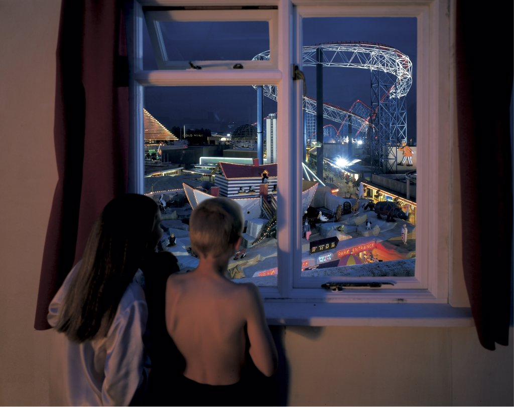 England, Lancashire, Blackpool. Children standing at a window looking at  the fun fair in Blackpool. : Stock Photo