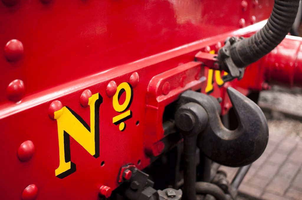 Stock Photo: 4282-18937 England, East Sussex, Horsted Keynes. A close up of painted text on a red steam engine at sheds in Horsted Keynes railway station in East Sussex.
