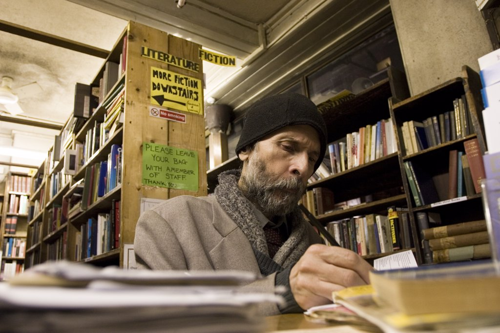 England, London, Charing Cross. Customer in second hand bookshop on Charing Cross Road. Second hand bookshops sell books of varying prices, the most expensive are in Cecil Court where more specialist antiquarian books are found. : Stock Photo