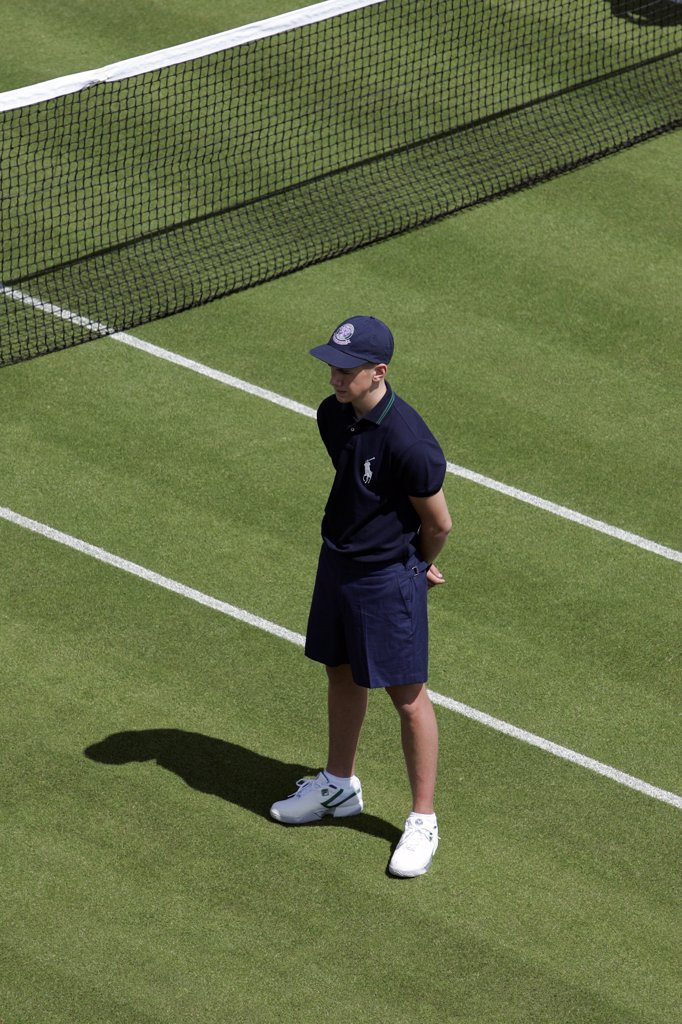 England, London, Wimbledon. A ball boy stands by the net during the Wimbledon Tennis Championships 2008. : Stock Photo