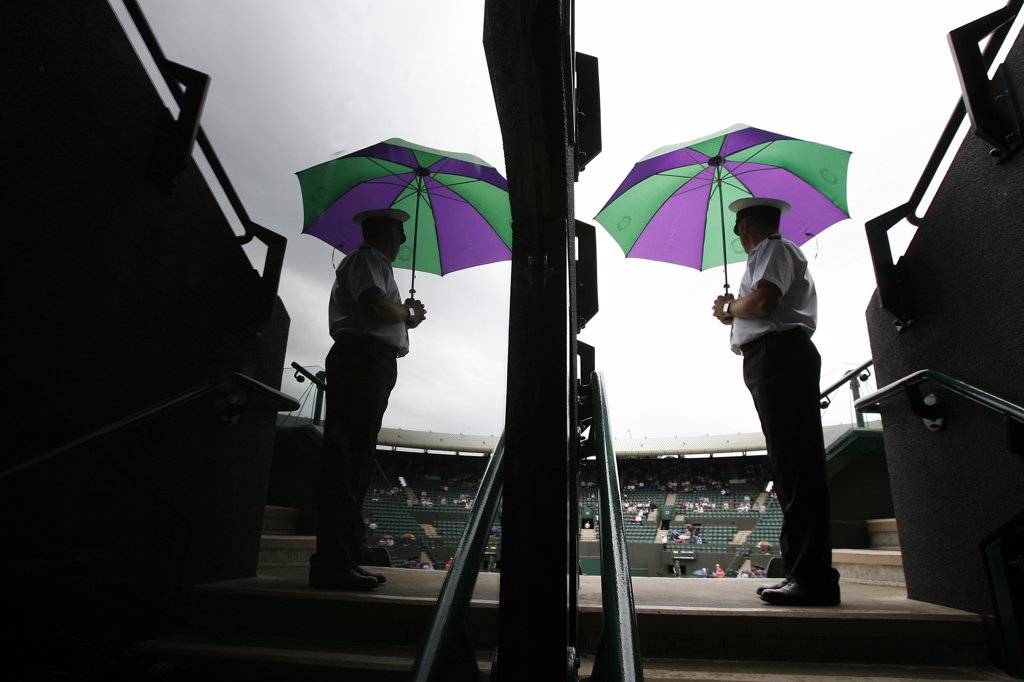 England, London, Wimbledon. A gate steward on court 1 with his umbrella at the Wimbledon Tennis Championships 2008. : Stock Photo