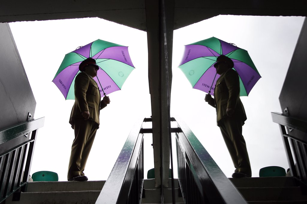 England, London, Wimbledon. A Service Steward and his umbrella is reflected in a glass pane in one of the entrances to centre court at the Wimbledon Tennis Championships 2008. : Stock Photo