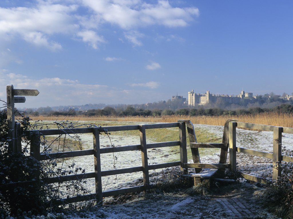 England, West Sussex, Arundel. Footpath and stile in frosty landscape on reed-lined embankment of River Arun with Arundel Castle beyond in winter. : Stock Photo