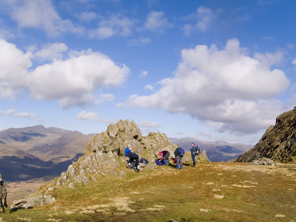 North Wales, Snowdonia, Cnicht. A group of walkers resting by rocks on the path up to Cnicht mountain with a view to Snowdon horseshoe beyond in Snowdonia National Park. : Stock Photo