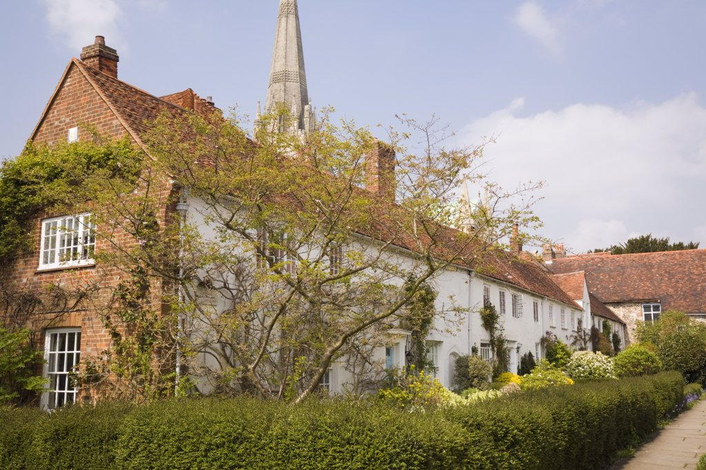 Stock Photo: 4282-19736 England, West Sussex, Chichester. A row of old cottages with the spire of The Cathedral Church of the Holy Trinity visible behind.