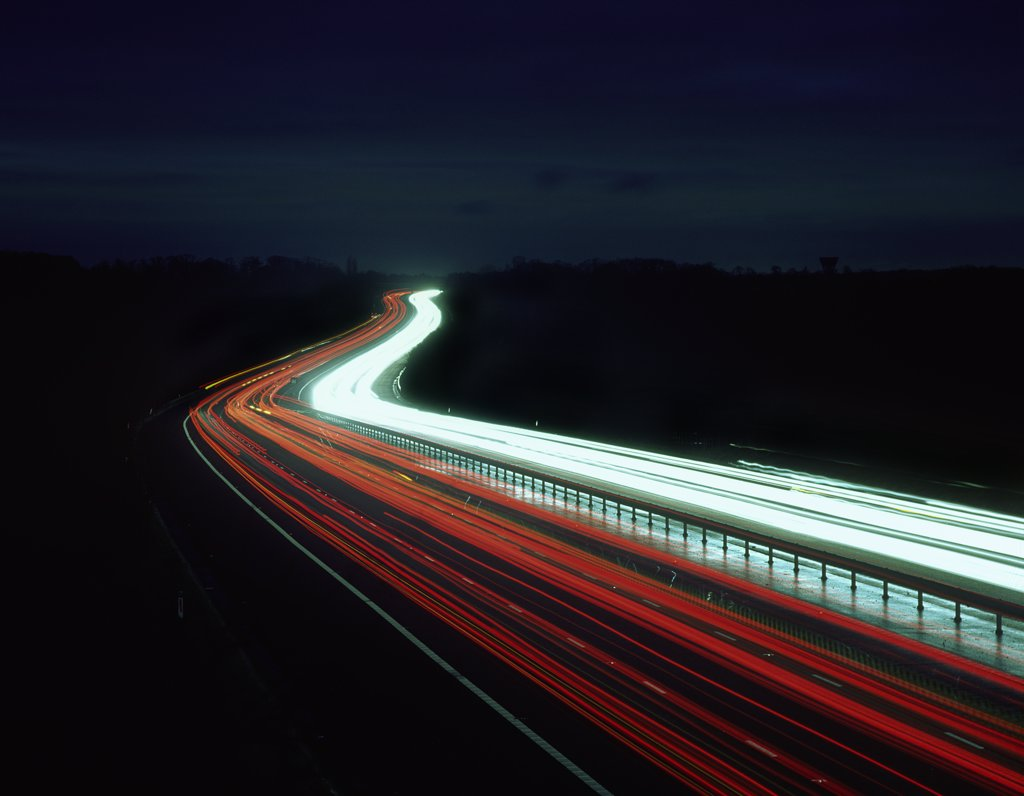 England, Essex, near Harlow. Light trails from traffic on the M11 motorway at night. : Stock Photo