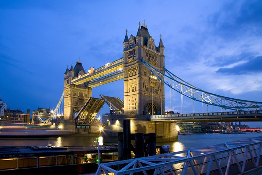 Stock Photo: 4282-20428 England, London, Tower Bridge. A boat passing under the raised bascules of Tower Bridge at Dusk.
