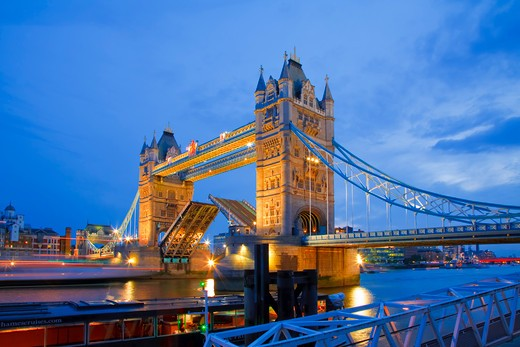 England, London, Tower Bridge. A boat passing under the raised bascules of Tower Bridge at Dusk. : Stock Photo