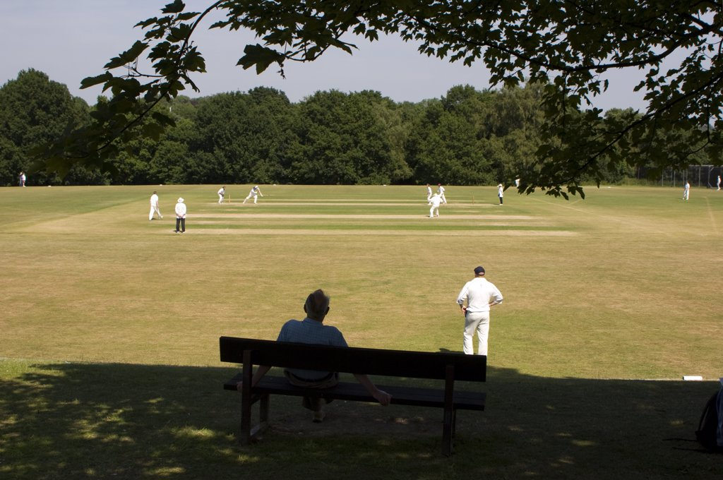 Stock Photo: 4282-2054 England, Hertfordshire, Harpenden. Cricket match being played on a village green.