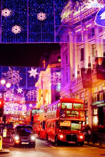 England, London, Regent Street. Double decker busses and and a black taxi cab waiting at traffic lights on Regent Street under the annual Christmas lights. : Stock Photo